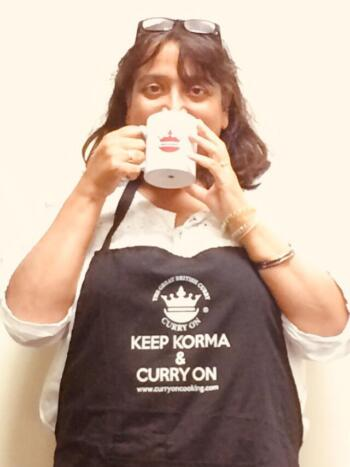 Spice Sister Veena Josh wearting a black apron and drinking from