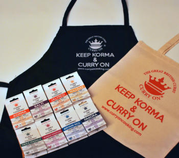 Black apron with curry on cooking logo with wording Keep Korma and Curry On with a cream shopper and 8 Curry On Cooking curry kits