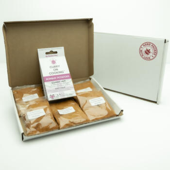 5 sachets 1 Bombay Potato Kit displayed in a letter postal box open with a closed box with a handpacked with love sticker
