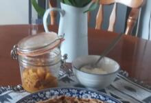 Indian stuffed flatbread on plate on table with pickle jar plus a jug of tulips