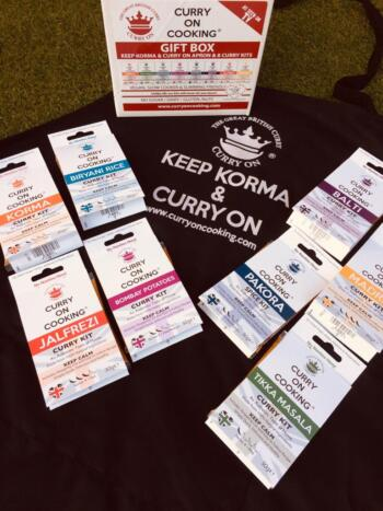 8 Curry On Cooking kits laid on top of a black apron with Keep Korma and Curry On